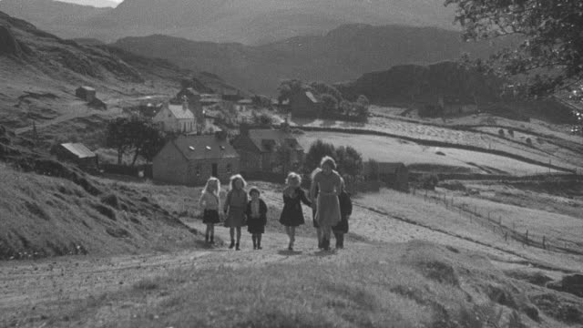1944 montage schoolmarm ringing bell as students walk up hill to schoolyard / achriesgill, scotland, united kingdom - achriesgill stock videos and b-roll footage