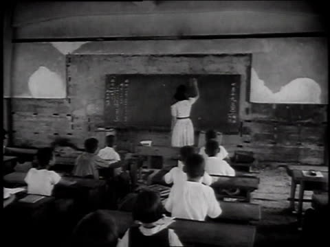 schoolteacher writing at blackboard / students taking notes - postwar stock videos & royalty-free footage