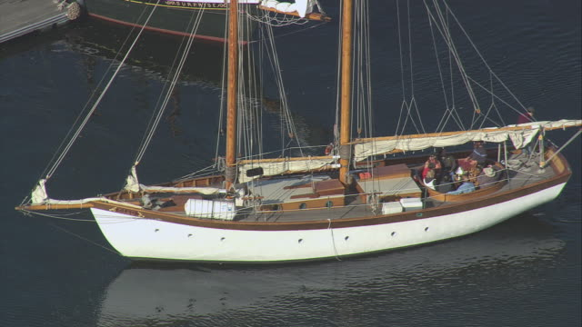 AERIAL Schooner in calm water, sails furled, motoring from marina past docked sailboat / Camden, Maine, United States