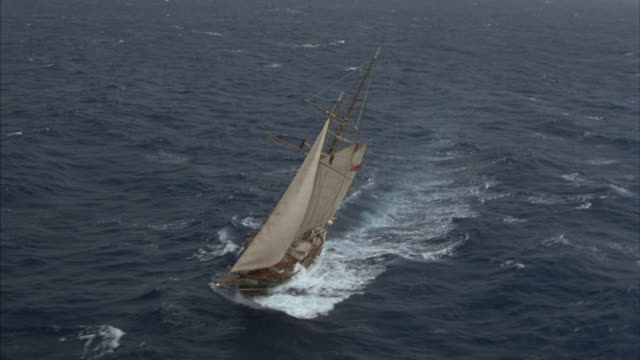 A schooner makes a turn under full sails at sea.