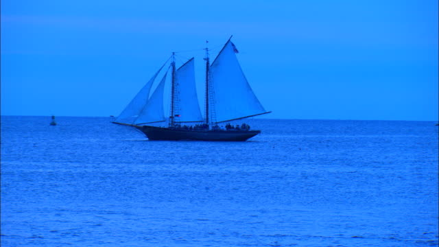 a schooner sails on the ocean at sunset. - sailing ship stock videos & royalty-free footage