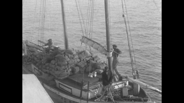 schooner slowly leaves its dock, heavily laden with items in sacks / note: exact day not known - 荒い麻布点の映像素材/bロール