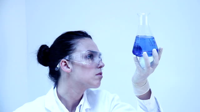 Science. Female lab worker and glass flask.