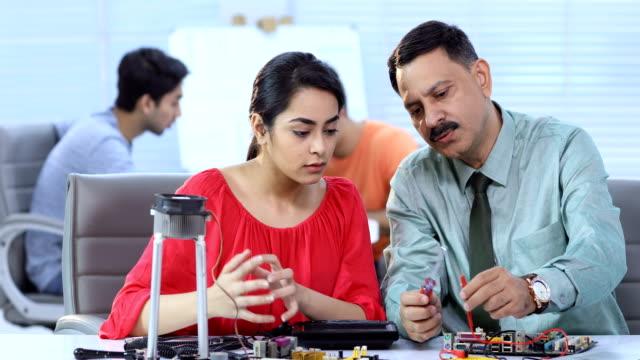 vídeos de stock, filmes e b-roll de ms pan science student and professor soldering wires in laboratory / delhi, india - camisa e gravata