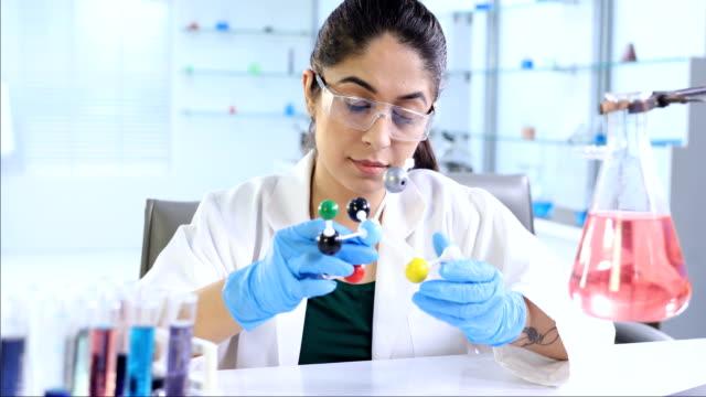 ms pan zi science student examining molecular structure in laboratory / delhi, india - pallone di vetro video stock e b–roll