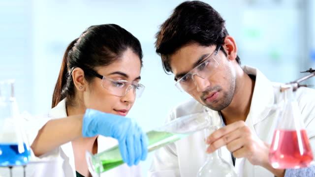 ms science students examining chemicals in laboratory / delhi, india - pallone di vetro video stock e b–roll