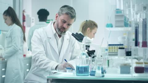 scienist schaut durch ein mikroskop - research stock-videos und b-roll-filmmaterial