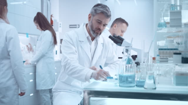 vidéos et rushes de scienist regarde à travers un microscope - concepts