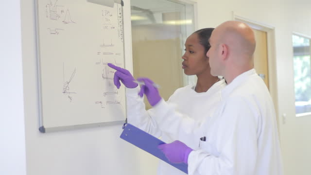 scientist analyze and discuss research data on white board in science laboratory - whiteboard stock videos & royalty-free footage