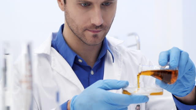 scientist are certain activities on experimental science like mixing chemicals or entry data to develop medicine - pallone di vetro video stock e b–roll