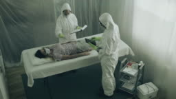 Scientist attending to a woman with a virus lying on a stretcher