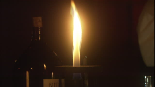 a scientist briefly holds a beaker over a bunsen burner. - bunsen burner stock videos & royalty-free footage