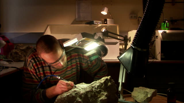 a scientist carves fossils out of a rock. - archaeology stock videos & royalty-free footage