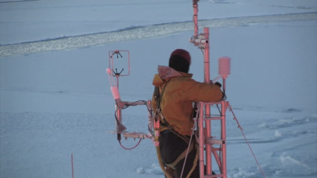 scientist cleans ice rime from sensitive monitoring equipment in the arctic september 18 2008 – from the historic 17month expedition involving 250... - climate scientist stock videos & royalty-free footage