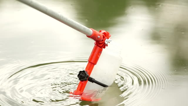 Scientist collecting dam water in bottle