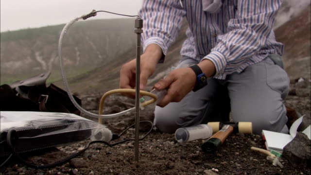a scientist collects samples from the ground surrounding mount usu in the shikotsu-toya national park. - geologist stock videos & royalty-free footage