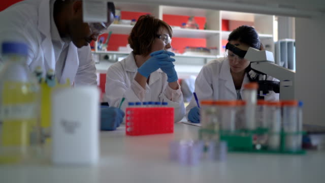 Scientist discussing with colleagues in laboratory