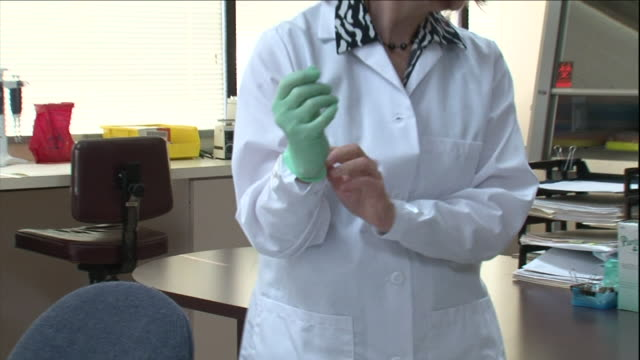 a scientist dons gloves as she prepares to work in a lab. - glove stock videos & royalty-free footage