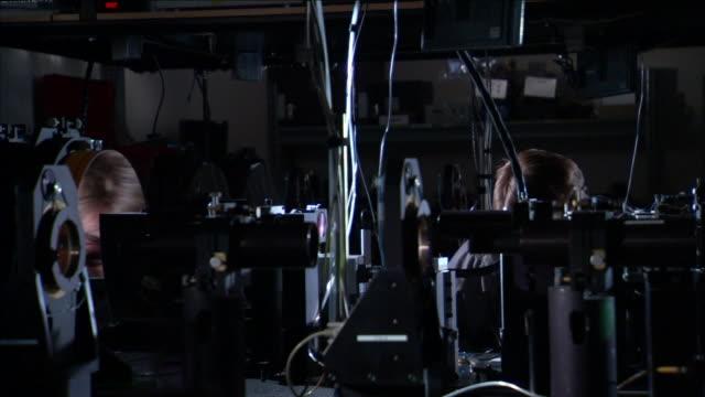a scientist examines equipment at starfire lab. - sehvermögen stock-videos und b-roll-filmmaterial