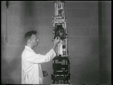 b/w 1952 scientist feeding astronaut monkey sitting on rocket structure / white sands nm - 1952 stock videos & royalty-free footage