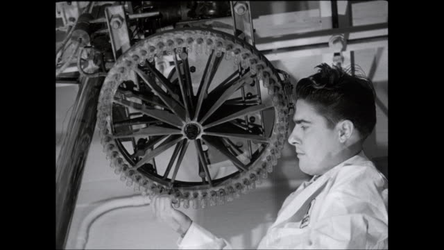 MS Scientist fixing test tubes on wheel shaped machine / United States