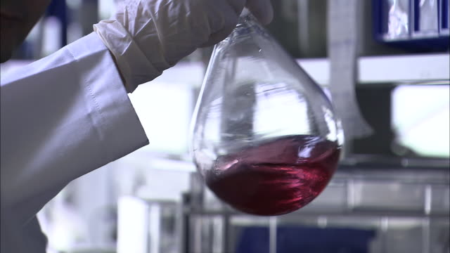 vídeos de stock e filmes b-roll de cu, focusing, scientist holding glass balloon shaped container with red liquid in genetic laboratory, close-up of hand, singapore - investigação genética