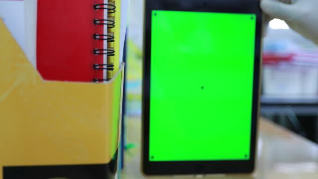 vídeos de stock e filmes b-roll de scientist holding green screen at bookshelf - capa de livro