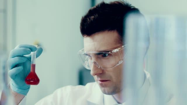 wissenschaftler in einem labor. medizinisches experiment - schutzbrille stock-videos und b-roll-filmmaterial