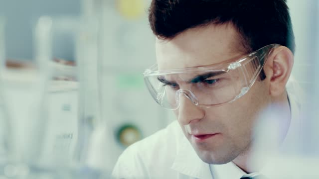 scientist in a lab. medical experiment - piastra petri video stock e b–roll
