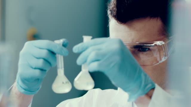 vídeos de stock e filmes b-roll de scientist in a lab. medical experiment - reacção química