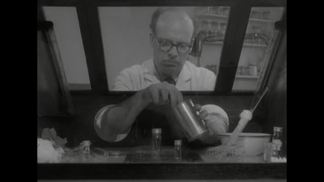 A scientist in a lab tests virus specimens in a glass box