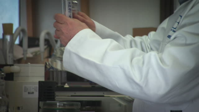 a scientist in a laboratory preparing vials for a shaker - household fixture stock videos and b-roll footage