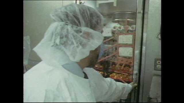 scientist in a mask and protective gear enters an aids laboratory storeroom, uk; 1986. - risk stock videos & royalty-free footage
