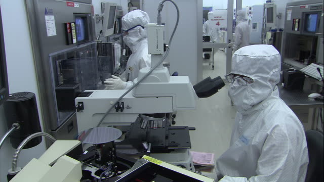 stockvideo's en b-roll-footage met a scientist in a sterile suit works with a microscope. - wetenschapper