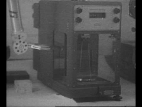 Scientist in atomic testing laboratory uses robotic arms to work with material in enclosed case / CU Albert Einstein uses eyeglasses to read aloud /...