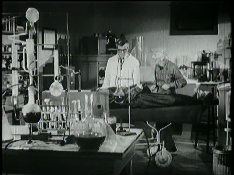 B/W 1958 scientist in lab examines body on table as senior man watches