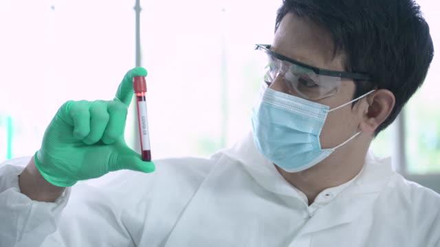 熱心な19の血液サンプル試験管を手で振る研究室の科学者 - shaking点の映像素材/bロール