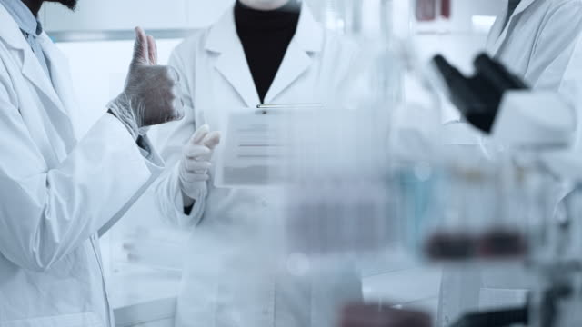 scientist in laboratorium holds the vial in his hand - epidemiology stock videos & royalty-free footage