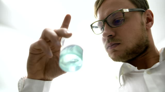 Scientist in laboratory examining liquid in glass beaker.