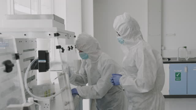 scientist in laboratory wearing protective coverall discussing science experiment test results - medical test stock videos & royalty-free footage