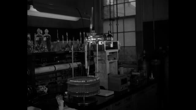 Scientist in laboratory with glassware and turntable where glass marbles drop onto tops of test tubes