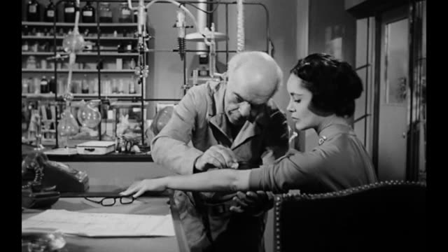 1959 scientist (michael mark) injects woman (susan cabot) with age defying serum - young animal stock videos & royalty-free footage
