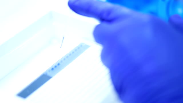 Scientist is mixing DNA on parafilm and loading into agarose,Slow motion