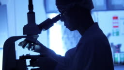 Scientist is using with microscope in dark