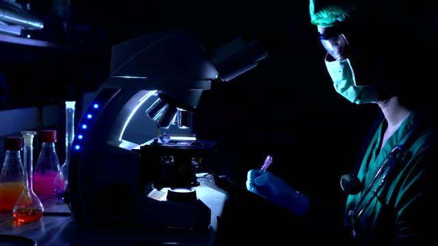 vidéos et rushes de scientifique est à l'aide de microscope en sihouette - biotechnologie