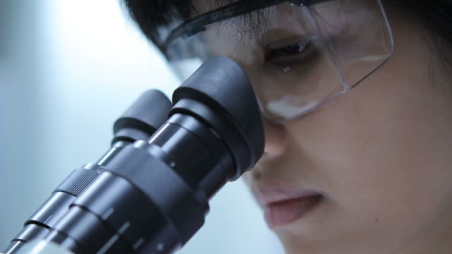 Scientist is using with microscope