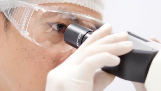 scientist is using with microscope - safety glasses stock videos & royalty-free footage