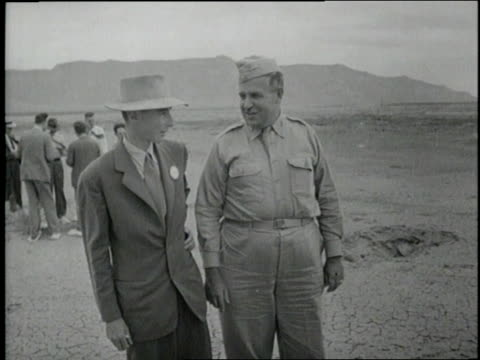 Scientist J Robert Oppenheimer and US General Leslie Groves talk together at an atomic test site in Los Alamos New Mexico