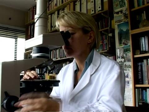 scientist looking in to microscope, ms - scienziata video stock e b–roll