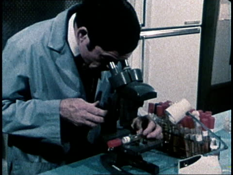1980 scientist looks at plant materials with microscope in laboratory / usa - 1980 stock videos & royalty-free footage